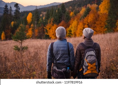 Happy couple feel freedom and enjoy the beautiful autumn forest in the mountains and looking together on sunset