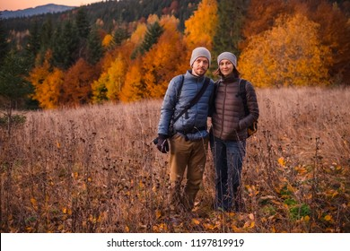 Happy couple feel freedom and enjoy the beautiful autumn forest in the mountains