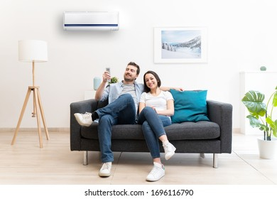 Happy couple freshen up using air conditioner at home - Shutterstock ID 1696116790