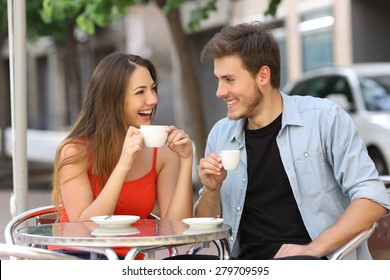 Happy couple or friends flirting talking and drinking in a restaurant terrace