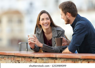 Happy couple or friends talking and drinking coffee in a rural apartment terrace on vacation