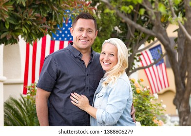Happy Couple In Front of Houses with American Flags.