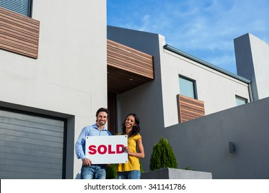 Happy couple in front of new house with sold sign