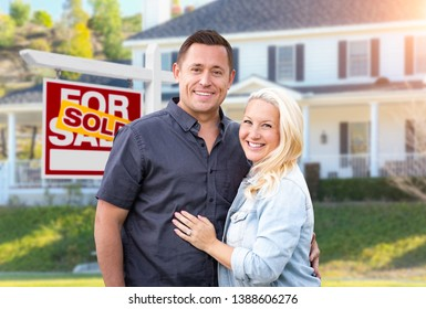 Happy Couple In Front of Sold Real Estate Sign and Beautiful House.