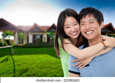 Happy couple in front of their house
