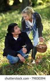 happy couple gathering mushrooms