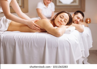 Happy couple getting back massage at spa