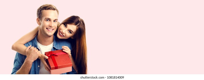 Happy couple with gift box, close to each other and looking at camera, with copyspace empty area for slogan or advertising text message, over pink background. Love, relations and celebration concept.