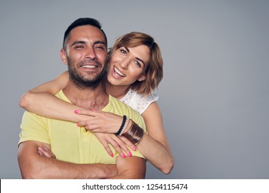 Happy couple, girl in love embracing boyfriend, over grey background