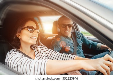 Happy couple goes by the car