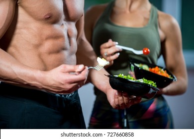 Happy couple in gym feeding each other with fresh salad at gym