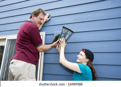Happy couple hanging a light fixture on a house.Horizontally framed photo.