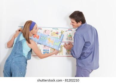 Happy couple hanging wallpaper in baby room