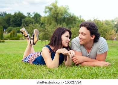 happy couple has a rest on a green grass in park