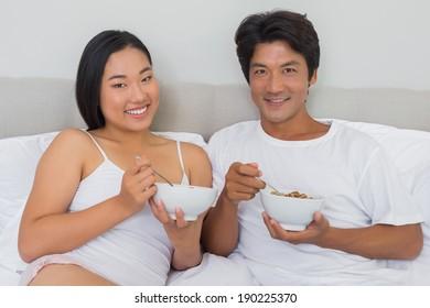 Happy couple having breakfast in bed at home in bedroom