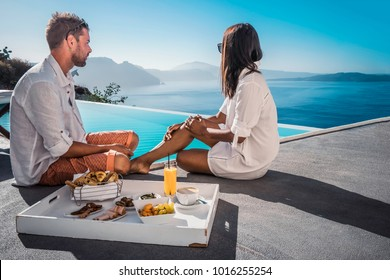 Happy couple having breakfast by the infinity pool looking out over the Caldera ocean of Santorini Greece on vacation