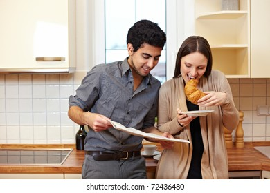 Happy couple having breakfast in the kitchen and reading newspaper