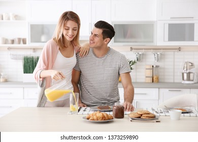 Happy couple having breakfast together in kitchen