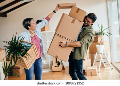 Happy couple having fun with carboard boxes while moving into new home.