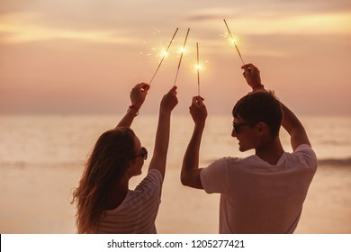 Happy couple having fun and celebrates sunset with sparklers in hands
