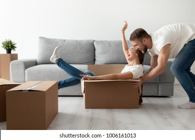 Happy couple having fun laughing moving into new home, young excited woman riding sitting in cardboard box while man pushing it, cheerful roommates playing while packing unpacking belongings together