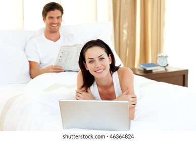 Happy couple having fun lying on the bed