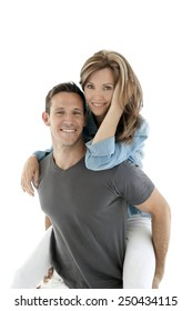 Happy couple having fun - man giving piggyback ride to woman - isolated