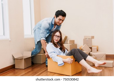 Happy couple having fun and moving woman sitting in a cardboard box at home