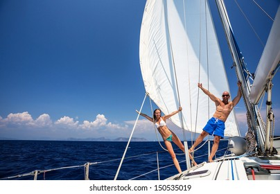Happy couple having fun on sailboat, young family in water cruise, yachting sport, active lifestyle, summer vacation, romantic trip, travel and tourism concept