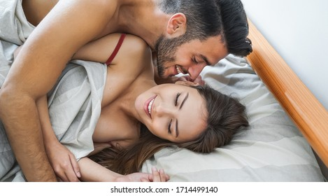 Happy couple having fun on bed under blanket - Young romantic lovers intimate moments - Intimacy and love relationship concept