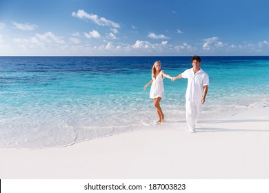 Happy couple having fun on the beach, spending honeymoon on luxury tropical resort, summer holidays, love concept