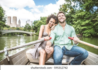 Happy couple having fun on a boat in Central Park - Interracial couple of tourists sightseeing Manhattan