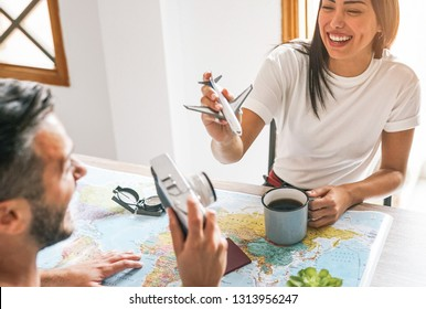 Happy couple having fun planning next world tour together - Young people getting ready for next trip using a travel map - Vacation, love and relationship concept