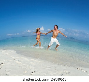 Happy couple having fun and running on a tropical beach in a sunny day