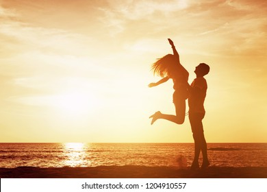 Happy couple having fun at sea beach. Silhouettes against sunset sky with place for text