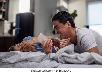 Happy couple having fun while lying on the bed and laughing about something funny on smart phone.