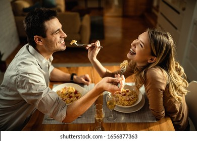 Happy couple having fun while feeding each other during a meal at dining table.