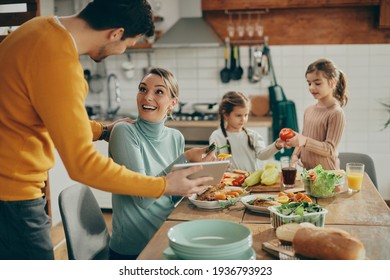 Happy couple having fun while using touchpad at dining table while their daughters are in the background. Focus s on woman.