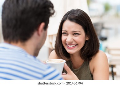 Happy couple having a great time talking over a cup of coffee