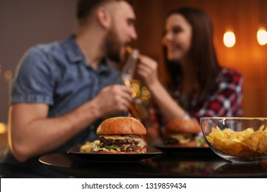 Happy couple having lunch in cafe, focus on burger