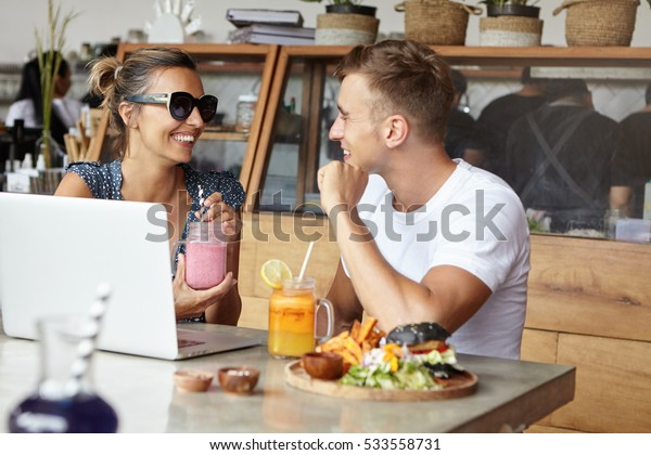 Happy couple having lunch together at cozy cafeteria, sitting in front of laptop computer. Pretty woman wearing sunglasses holding glass of smoothie and talking to her handsome friend in white t-shirt