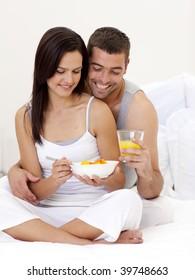 Happy couple having nutritive breakfast sitting in bed