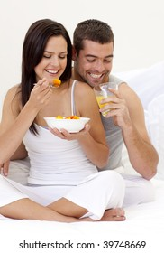 Happy couple having nutritive breakfast in bed