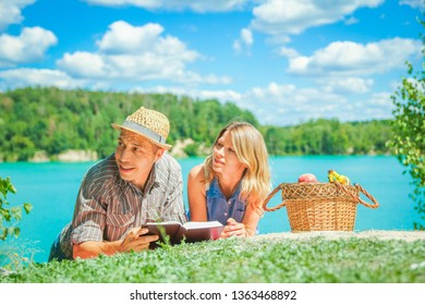 happy couple having picnic by the sea in nature