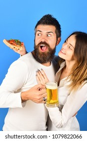 Happy couple having pizza for lunch. Happy family enjoy eating italian food. Smiling couple eating homemade pizza together. Happy family - husband drinking beer, wife holds slice of yummy pizza.