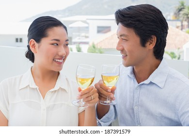 Happy couple having white wine outside on a balcony
