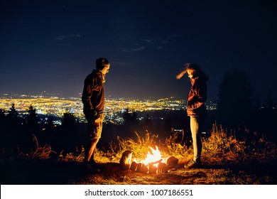 Happy couple hikers near campfire under night sky and city lights at background