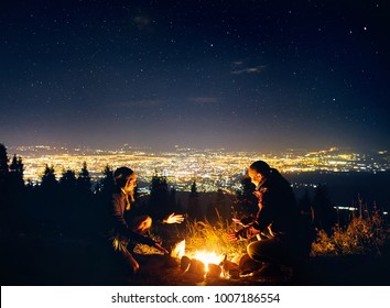Happy couple hikers warm they hands near campfire under night sky with stars and city lights at background