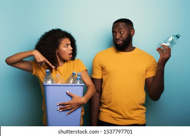 Happy couple hold a plastic container with bottles over a light blue color. Concept of ecology, conservation, recycling and sustainability