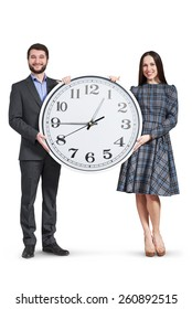 happy couple holding big clock and smiling. isolated on white background